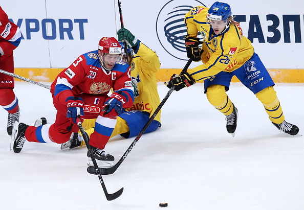 Sweden's youthful winger Oskar Lindblom (# 26) from IF Brynas Galve competes for the loose puck with Russia' captain Pavel Datsyuk (# 13) from SKA St. Petersburg, the highly experienced 38-year-old veteran who racked up 918 points in 958 National Hockey League games over the course of fourteen seasons for the Detroit Red Wings, during the recent 2016 Channel One Cup international match which was played at the VTB Ice Palace in Moscow ..... (photo courtesy Artyom Korotayev / TASS)